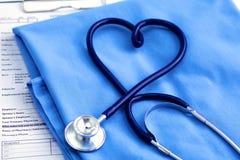 Медицинский стетоскоп переплел в форме сердца лежа на терпеливом крупном плане формы доктора списка и сини истории болезни Стоковое Изображение RF