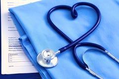 Медицинский стетоскоп переплел в форме сердца лежа на терпеливом крупном плане формы доктора списка и сини истории болезни Стоковые Изображения