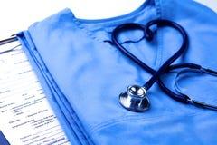 Медицинский стетоскоп переплел в форме сердца лежа на терпеливом крупном плане формы доктора списка и сини истории болезни Стоковая Фотография