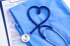 Медицинский стетоскоп переплел в форме сердца лежа на терпеливом крупном плане формы доктора списка и сини истории болезни Стоковое фото RF