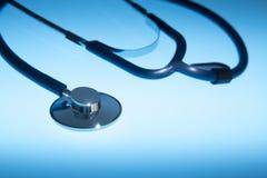 Медицинский стетоскоп драматически осветил против голубой предпосылки стоковое изображение