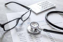 Медицинское treatmant заявление выписывания счетов с стетоскопом и стеклами на каменной предпосылке стоковое фото