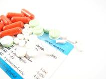 Медицины на карточке медицинской страховки, показанной преимущества группы, изолированные на белой предпосылке Стоковое фото RF
