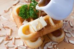 Мед конца-вверх лить от верхней части waffles и гайки Стоковая Фотография