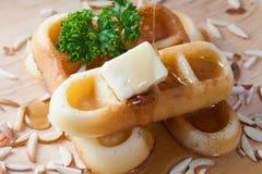 Мед конца-вверх лить от верхней части waffles и гайки Стоковая Фотография RF