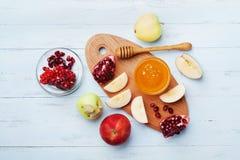 Мед, куски яблока и гранатовое дерево служат на взгляд сверху доски кухни Таблица установила с традиционной едой на еврейский пра стоковое фото rf