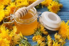 Мед пчелы в стеклянном опарнике и букет цветя одуванчиков Стоковое Изображение