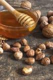 Мед пчелы в стеклянном опарнике, фундуках и грецком орехе, на старом деревянном столе vintag Стоковое Фото