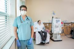 Медсестра в защитной одежде с пациентом Стоковое Фото