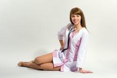 Медсестра детенышей с усаживанием и усмехаться стетоскопа стоковое изображение rf