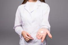 Медсестра женщины держа пилюльки в руке и показывая вверх изолированные большие пальцы руки Стоковое Фото