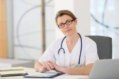 Медсестра женщины сидя на офисе больницы Стоковое фото RF