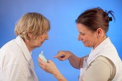 Медсестра измеряла температуру пожилой женщины Стоковые Изображения RF