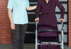 Медсестра и пожилая женщина в ходоке снаружи Стоковое фото RF