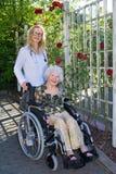 Медсестра и пожилые люди на кресло-коляске усмехаясь на камере Стоковое Фото