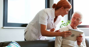 Медсестра и старший пациент используя планшет