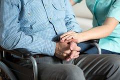 Медсестра касающая вручает ее пациента Стоковая Фотография