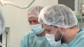 Медсестра обтирает лоб ` s хирурга на хирургии видеоматериал