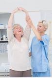 Медсестра помогая женскому пациенту в оружиях повышения стоковая фотография rf