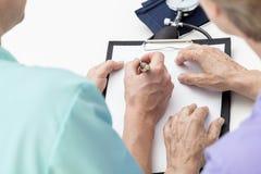 Медсестра принимая примечания Стоковые Фото