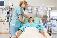 Медсестра регулируя подушку пациента стоковые изображения