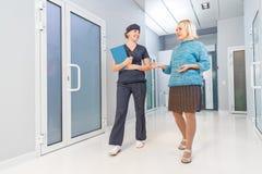 Медсестра с прогулкой пожилой женщины терпеливой вдоль залы Стоковое Изображение