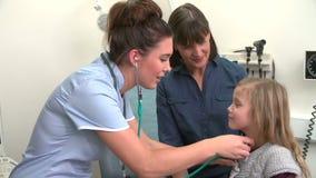 Медсестра слушая к комоду ребенка в хирургии сток-видео