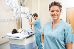 Медсестра усмехаясь пока коллега подготавливая пациента стоковое изображение rf