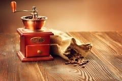 Мельница кофе с мешочком из ткани полным зажаренных в духовке кофейных зерен стоковое фото