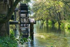 Мельница колеса воды на реке с зелеными деревьями на предпосылке Стоковая Фотография