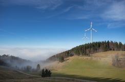 Мельницы энергии ветра над туманом в черном лесе, Германии Стоковые Фотографии RF