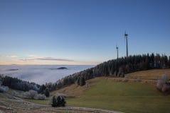 Мельницы энергии ветра над туманом в черном лесе Стоковое Изображение RF