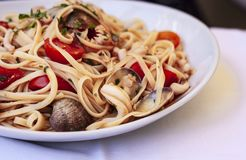 Мидии желания linguine спагетти макаронных изделий морепродуктов, clams, томаты вишни, свежий пармезан на белой плите в ресторане стоковые изображения