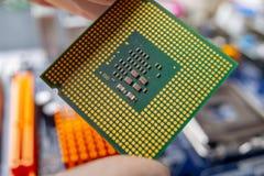 Микропроцессор обломока в руках техника инженера для компьютеров Высокая технология и микросхема ремонта стоковая фотография