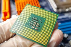 Микропроцессор обломока в руках техника инженера для компьютеров Высокая технология и микросхема ремонта стоковое фото rf