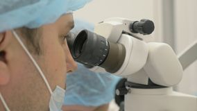 Микроскоп используемый доктором Дантист обрабатывает пациента в современном зубоврачебном офисе Работа ортодонта с ассистентом де видеоматериал