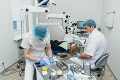 Микроскоп используемый доктором Дантист обрабатывает пациента в современном зубоврачебном офисе Деятельность унесена используя ко стоковая фотография rf