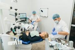 Микроскоп используемый доктором Дантист обрабатывает пациента в современном зубоврачебном офисе Деятельность унесена используя ко стоковые изображения rf