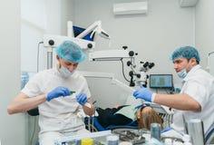 Микроскоп используемый доктором Дантист обрабатывает пациента в современном зубоврачебном офисе Деятельность унесена используя ко стоковые изображения