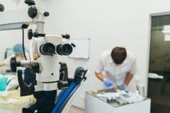 Микроскоп используемый доктором Дантист обрабатывает пациента в современном зубоврачебном офисе Деятельность унесена используя ко стоковое фото rf
