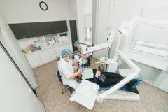 Микроскоп используемый доктором Дантист обрабатывает пациента в современном зубоврачебном офисе Деятельность унесена используя ко стоковое фото