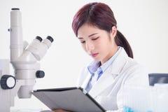 Микроскоп пользы ученого женщины стоковое фото rf