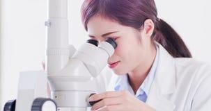 Микроскоп пользы ученого женщины стоковые изображения