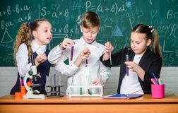 Микроскоп химии Маленькие ребята уча химию в лаборатории школы студенты делая эксперименты по биологии с микроскопом стоковая фотография rf