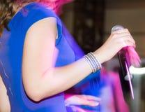 Микрофон в руках девушки на этапе Стоковое фото RF