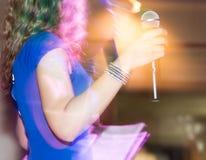 Микрофон в руках девушки на этапе Стоковое Изображение RF