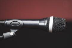 Микрофон крупного плана черный вокальный установил на стойке mic, расплывчатом красном темном bcakground Стоковые Фото