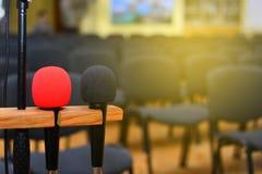 Микрофон над запачканными залой или семинаром бизнес-конференции стоковое изображение