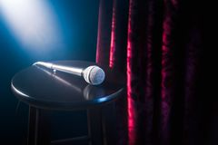 Микрофон на деревянной табуретке на этапе комедии стойки вверх с рефлекторами излучает, сверхконтрастное изображение стоковые фотографии rf