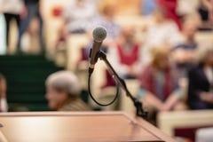 Микрофон на конспекте запачканном речи в конференц-зале или говоря свете конференц-зала, предпосылке события стоковые фотографии rf